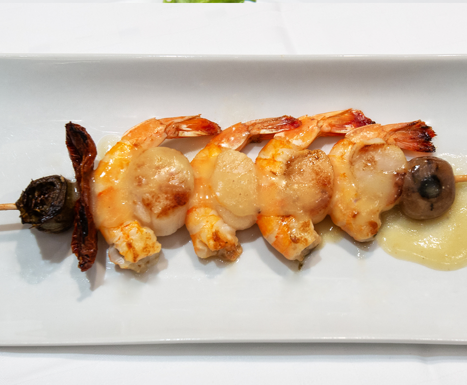 Brocheta de Vieiras Frescas y Langostinos Salvajes con Flor de Alcachofa en Salsa Emulsionada de Curry y Aceite de Marisco